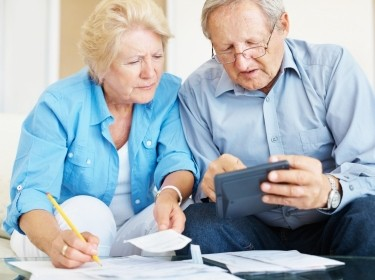 Elderly couple looking at bills and using a calculator