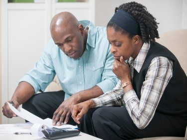 A couple looking at financial documents with a calculator