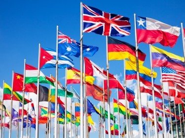 Group of international flags against a blue sky