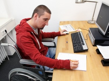 Man in wheelchair working in office