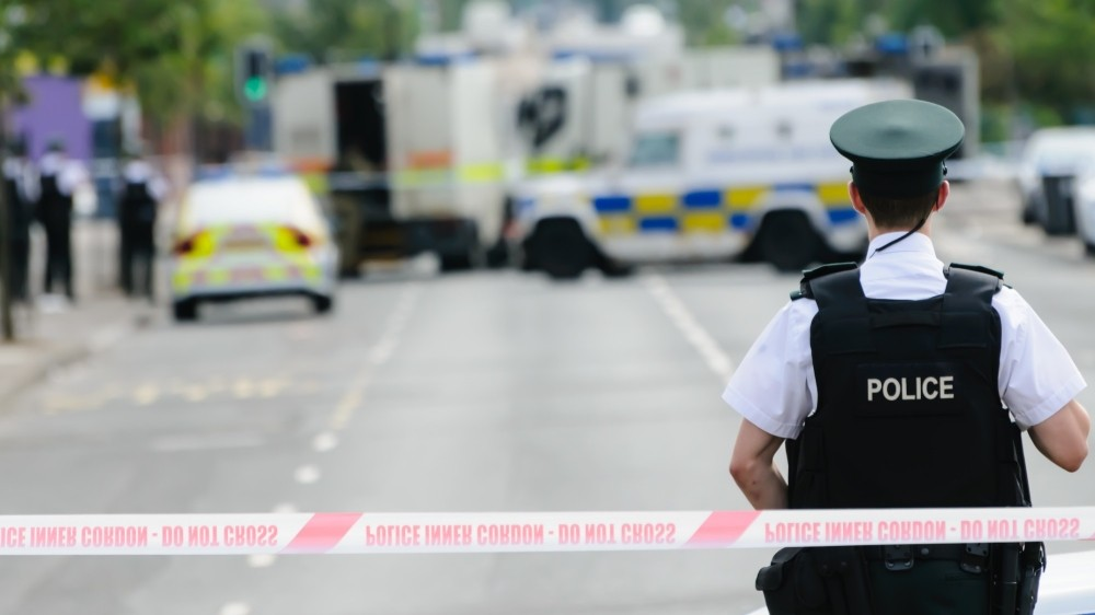 Police officer stands guard at a Police cordon point while army ATOs deal with a suspect bomb, photo by Stephen/Adobe Stock