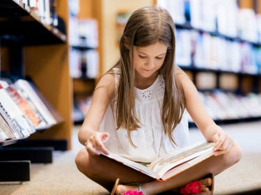 Little girl sitting on the floor reading a book
