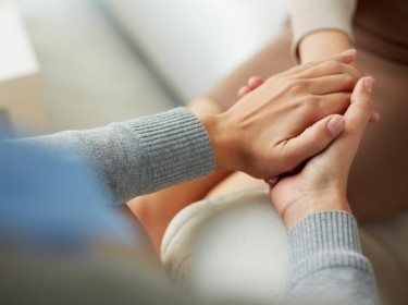 Woman holding another's hands, showing compassion, photo by pressmaster/Adobe Stock