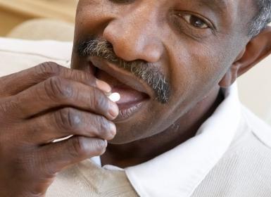 black man taking pill