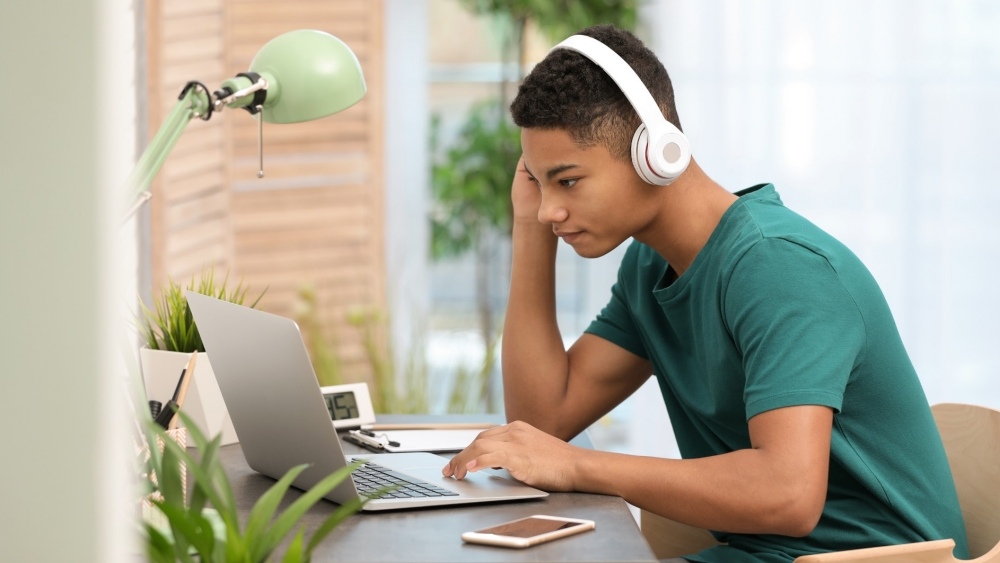 Black teenage boy with headphones using a laptop, photo by New Africa/Adobe Stock