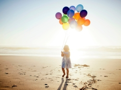 Girl with balloons, walking on beach