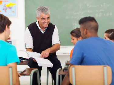 High school teacher teaching group of students in classroom
