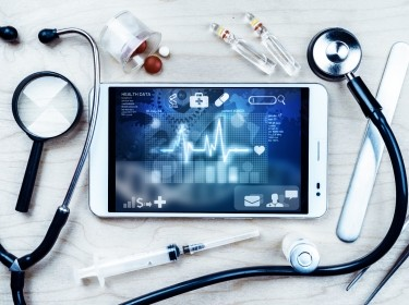 Tablet pc with healthcare mobile apps, and medical objects on a desk