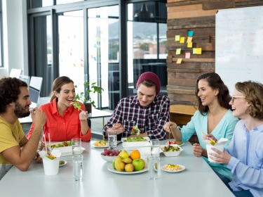Smiling employees having meal in office lunchroom, photo by WavebreakMediaMicro/Adobe Stock