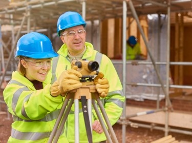 A female construction worker learns to use a builder's level