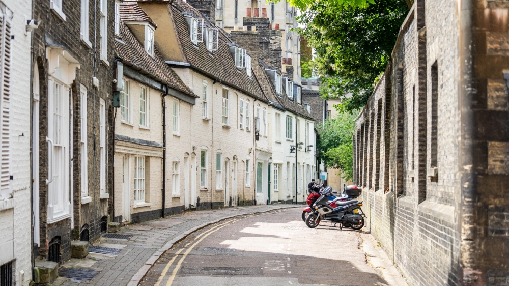 Bicycles and scooters parked outside terraced houses along a narrow street in Cambridge, photo by Powerofflowers/Adobe Stock