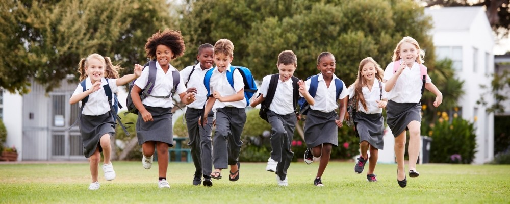 education, school, group, pupils, students, outdoors, break, breaktime, recess, playing field, uniform, playing, grass, running, active, fun, game, going home, rucksack, backpack, elementary, primary, learning, child, children, boy, girl, african american, black, asian, caucasian, multi-cultural, male, female, together, 8 years old, 7 years old, horizontal, front view, people, person, happy, smiling, excitement, private school, public school, independent school