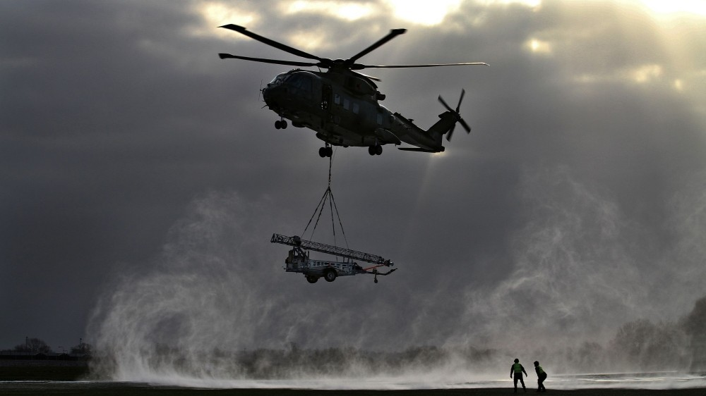 A Merlin helicopter comes in to drop off a Remover 3.1 mast during a snowy morning whilst on a helicopter flight trial at JADTEU, RAF Brize Norton, photo by 1st SAC David Turnbull/Royal Air Force Open Government License