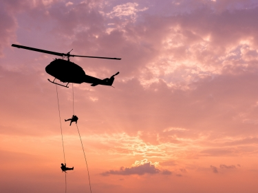 Silhouette of helicopter with soldiers conducting rescue operation