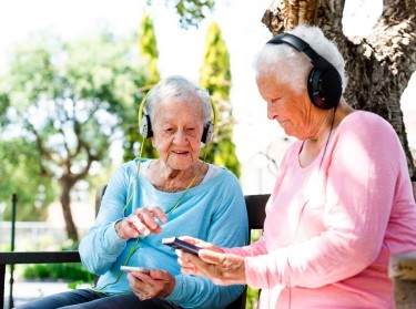 Two happy elderly women sitting on a bench outdoors using earphones to listen to music on their smart phones