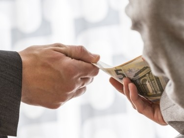 Businessman or politician taking bribe from a colleague handing him Euros