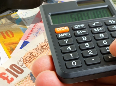 A hand with a calculator against various European bills