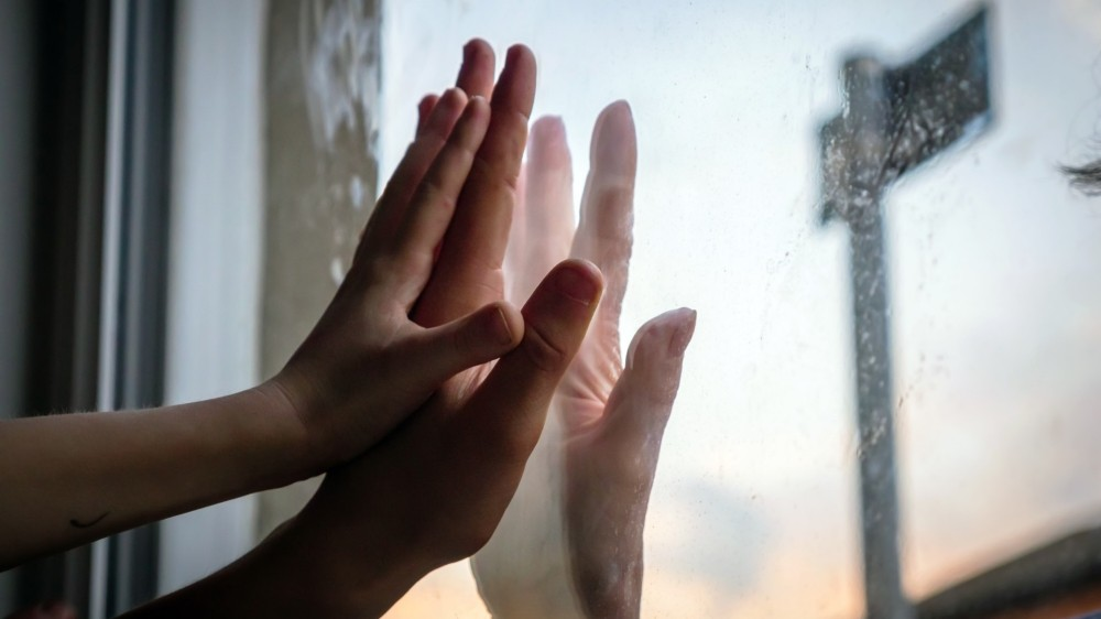 Hands of women and a child on opposite sides of window pane,  photo by Jevanto Productions/Adobe Stock