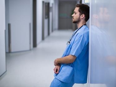 Tensed male nurse leaning on wall in corridor, photo by WavebreakmediaMicro/Adobe Stock