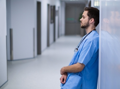 Tensed male nurse leaning on wall in corridor, photo by WavebreakmediaMicro/Adobe Stock