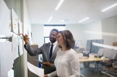 Businessman and businesswoman discussing hanging paperwork in office