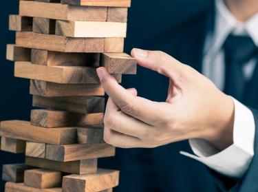 Businessman playing block tower game