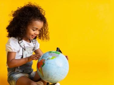 Little girl pointing to world globe, photo by Konstantin Postumitenko/Adobee Stock