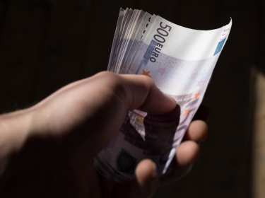 A pack of banknotes in hand with a face value of five hundred euros, photo by Evgeny Savchenko/Adobe Stock.