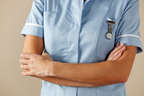 UK nurse standing with arms folded, photo by Monkey Business Images/Adobe Stock