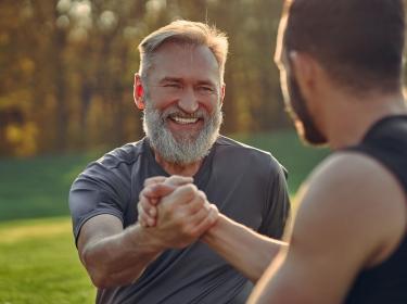 Two men greeting outdoors, photo by Viacheslav Peretiatko/Adobe Stock