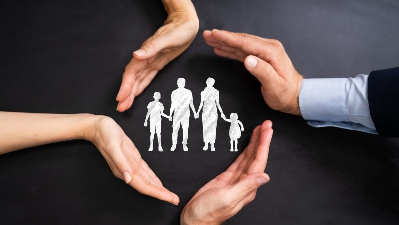 Four hands encircling image of a family, photo by Andrey Popov/Adobe Stock