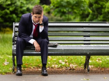 A dejected young businessman sitting alone on a park bench in London on a rainy day, photo by RichLegg/Getty Images