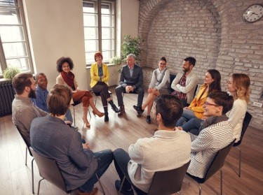 Business people talking at group meeting, photo by Igor Mojzes/Adobe Stock