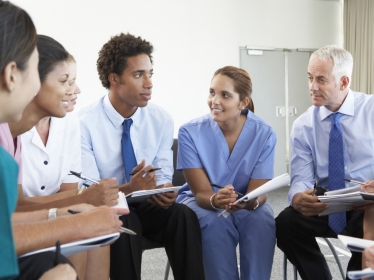 Medical staff seated in a circle at a case meeting