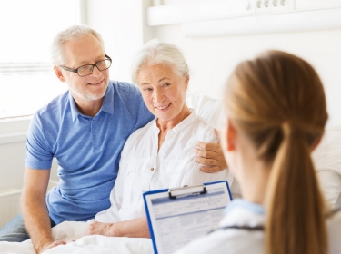 Senior woman and man talking to doctor with clipboard