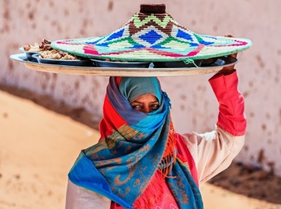 Muslim woman carrying food on her head in a Nubian village