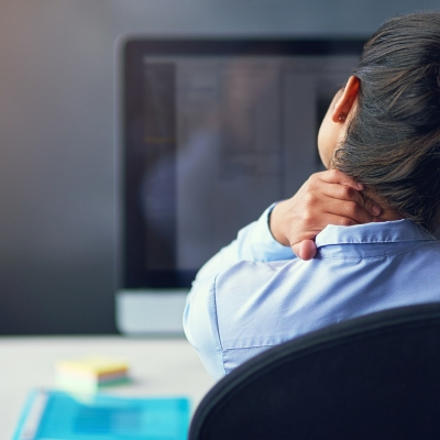 Businesswoman suffering from neck pain at the office