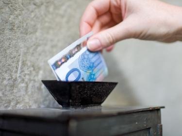 Person placing euros in a church donation box