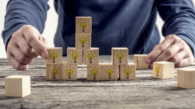 Man arranging wooden blocks with hand-drawn yellow lightbulbs, photo by Gaj Rudolf/Adobe Stock