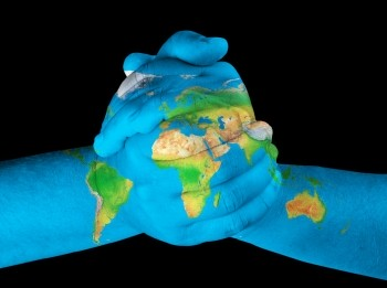 clasped hands painted with image of globe