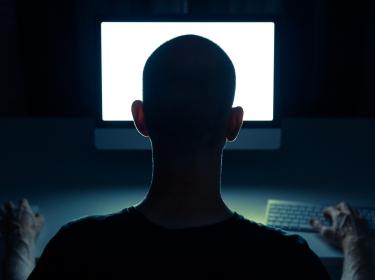 Silhouette of man in front of computer screen, photo by Sander van der Werf/Adobe Stock