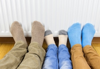 Family warming their feet in front of home radiator, photo by Evgen/Adobe Stock