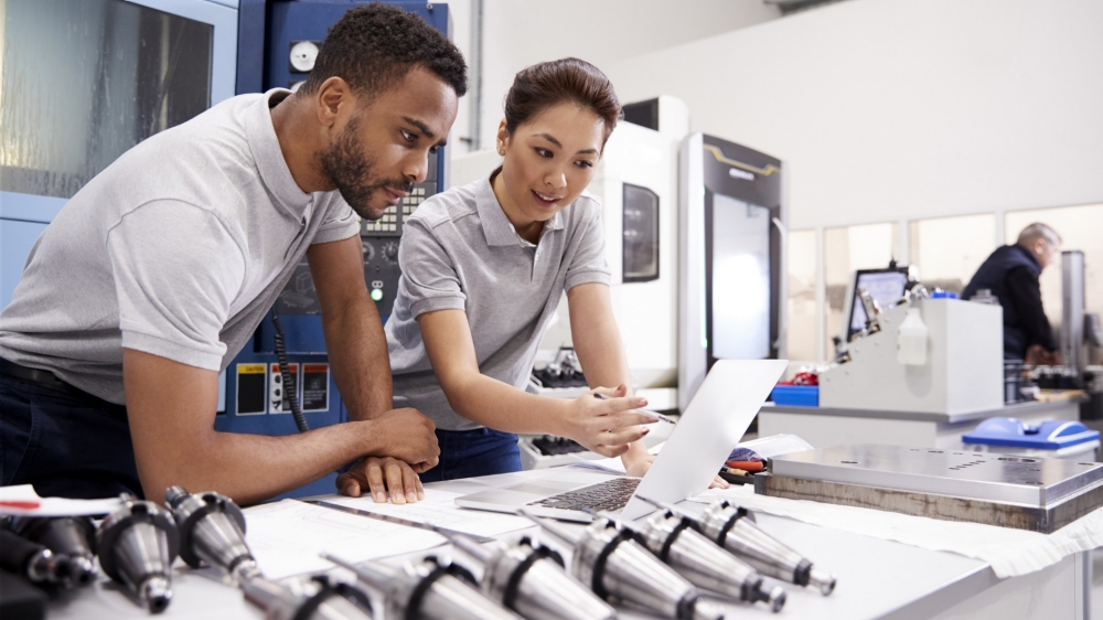 Two engineers using CAD programming software on laptop, photo by Monkey Business Images/Adobe Stock