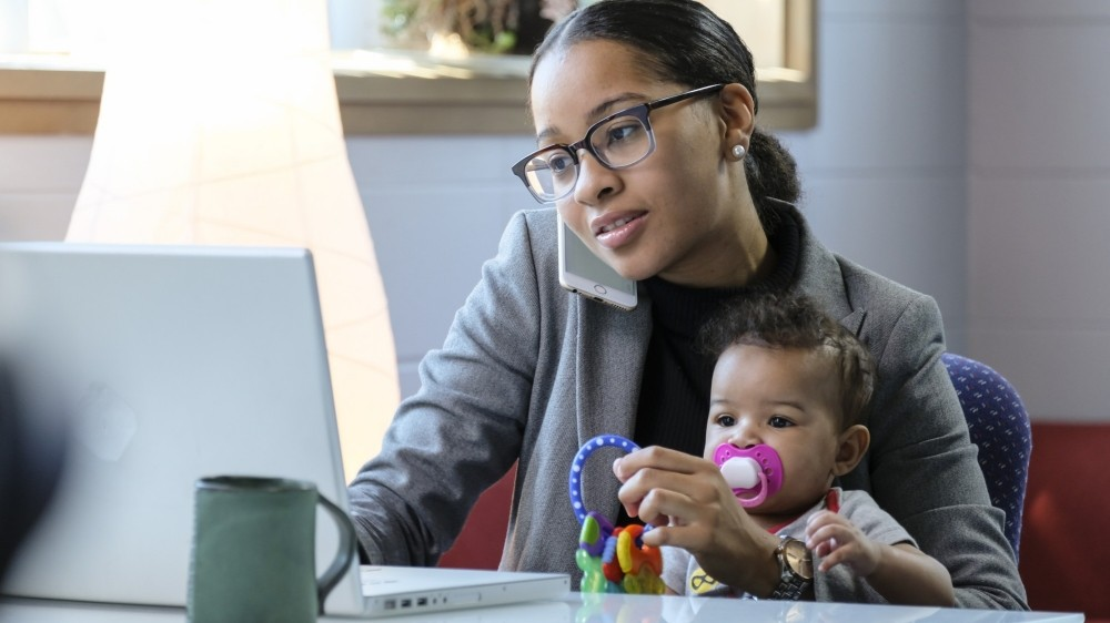 Mother holding baby and working at her computer, photo by Burlingham/Adobe Stock