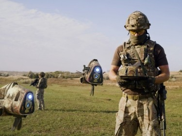 Military man launching drones in field, photo by Framestock/Adobe Stock