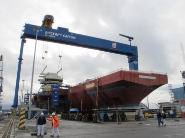 The forward island of the Queen Elizabeth-class aircraft carrier being attached to the main body of the carrier