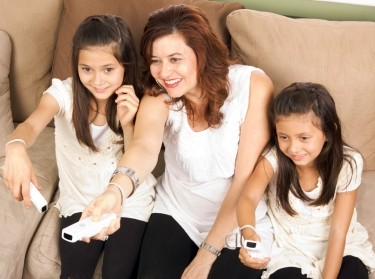 Family of mother and daughters playing video games together
