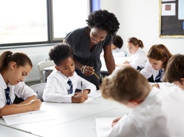Young high school teacher helping students, photo by Monkey Business Images/Adobe Stock