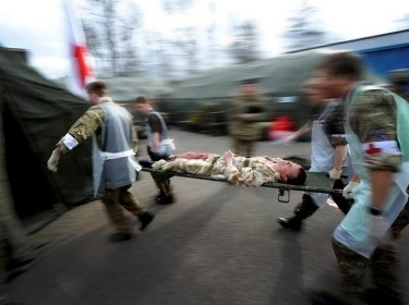 Medical staff with the UK's Army Medical Services rush a mock casualty into a resuscitation suite during a training exercise