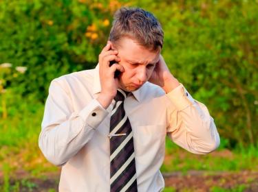 Businessman talking on a cell phone near a broken-down car